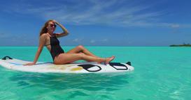 v11984 one 1 beautiful young girl in bikini sunbathing on surfboard paddleboard Footage