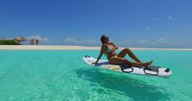 v11999 one 1 beautiful young girl in bikini sunbathing on surfboard paddleboard Footage