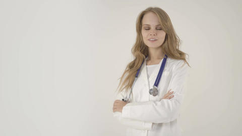 Young smiling female doctor with arms crossed on white... Stock Video Footage