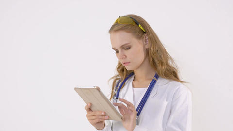 Happy female doctor using tablet computer on a white background Footage