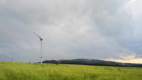 Lonely electric windmill in the field and rainy sky time lapse stock footage Footage