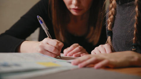 Mother and daughter doing a school homework assignment. Mom helps to deal with Footage