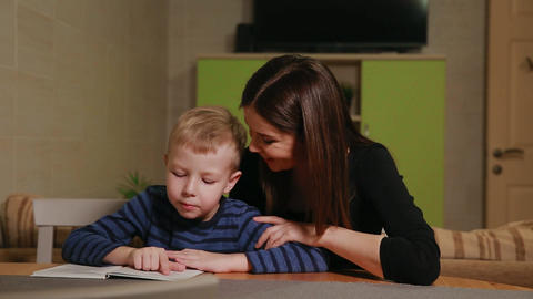 Mother and son sitting in the kitchen of his house and learning to read book Footage