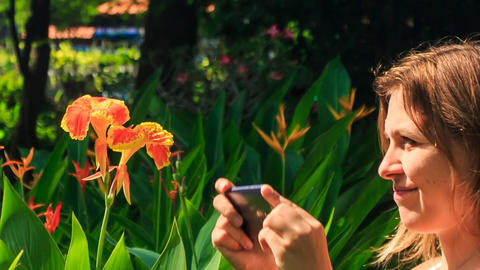 Blond Girl Smells at Tropical Flower Takes Photo in Park Footage