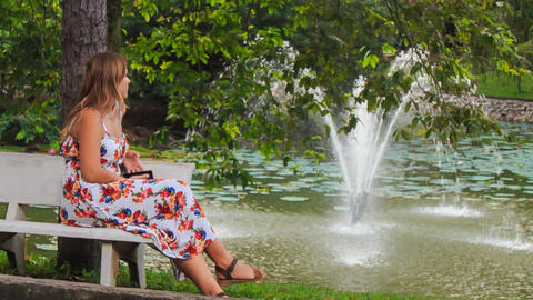 Blond Girl Sits on Bench at Fountain with Iphone in Park ビデオ
