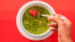Hand Takes Red Heart away of Green Soup on Red Table Footage