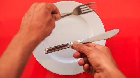 Hands Put Fork Knife Horizontally on Plate on Red Table Footage