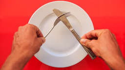 Hands Put Fork Knife At Acute Angle On Plate On Red Table stock footage