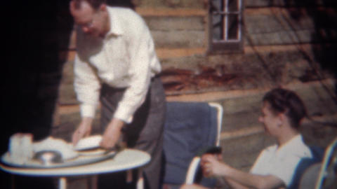 1944: Man serving fancy food to wife at vacation log cabin outdoor dining ライブ動画