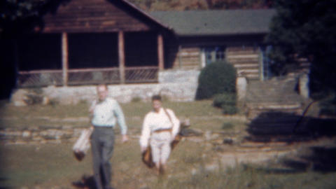 1945: Couple leaving log cabin going golfing carrying golf bags ライブ動画