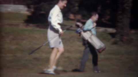 1945: Man caddy woman golfer carries golf clubs bag down fairway Footage