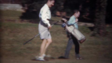 1945: Man caddy woman golfer carries golf clubs bag down fairway Footage