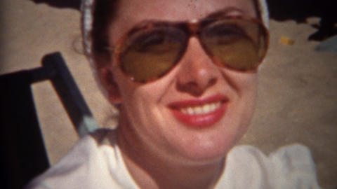 1944: Sunglasses woman smoking cigarette at the beach smiling big Footage
