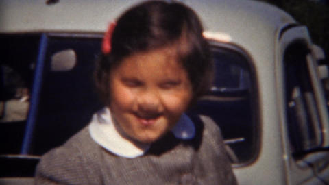 1944: Cute child in grey schoolgirl uniform outdoor gray classic car leaning Footage