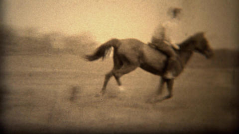 1937: Men jumping horses over fence loses hat in wooded rural area Footage