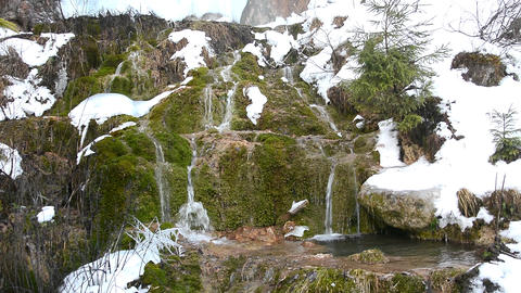 Mountain stream flowing over a frozen waterfall among rocks covered with green m Footage