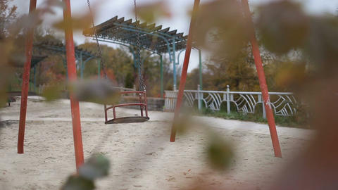 Empty playground swing swaying in autumn time Archivo