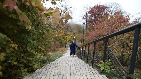 Charming woman walking up the stairs in fall Footage
