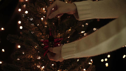 Female decorate Christmas tree with star decoration on bokeh lights background Footage