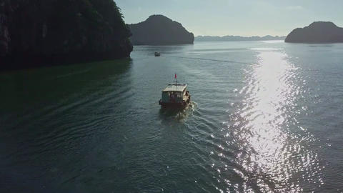 Drone Follows Tourist Boat on Tranquil Bay along Sun Path Live Action