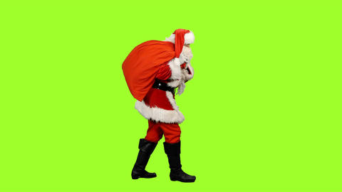 Santa Claus carrying gifts in sack on green background Footage