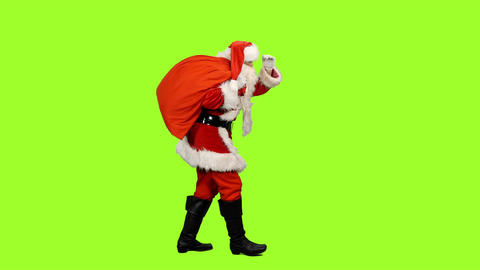 Santa Claus goes with gifts bag looks into the distance on green background Footage