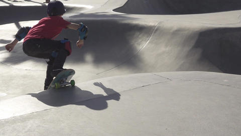 Young boy skateboards in skate park near palm trees Footage
