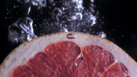 fresh grapefruit plunging in water, slow motion ビデオ