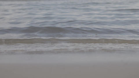 Timelapse background of small waves rippling onto shore Footage