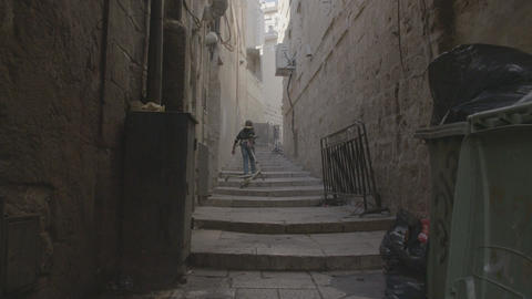 A young boy pulls a wheeled object up a set of old steps Footage