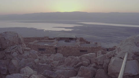 Camera rises above rocks to show ancient city near water 2 Footage