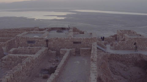 Camera rises above rocks to show sunrise over ancient city Footage