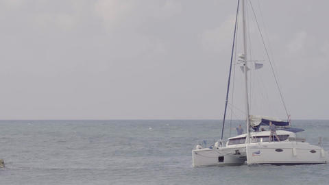 White catamaran boat approaches rocky shore Footage