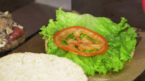 Macro Cook Puts Fresh Tomatoes on Salad for Preparing Hamburger Footage