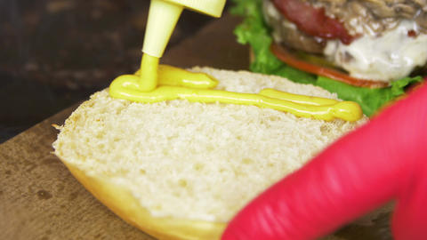 Macro Person Pours Mustard on Bun for Cooking Hamburger Live Action