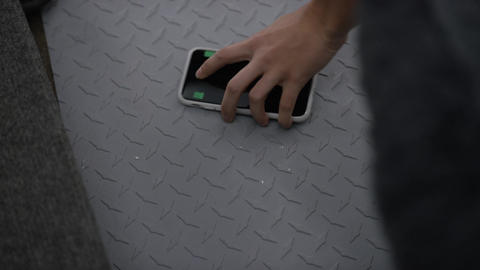 Hand picks up phone with tracking marks from metal surface Footage
