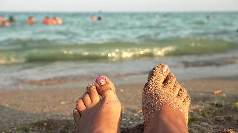 She looks over her legs with wet sand on them on the high seas where children pl Footage