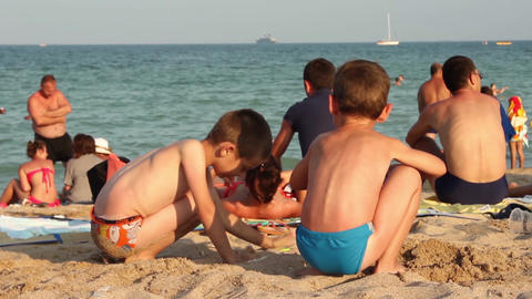 Children playing in the sand on the seashore, while parents looking at the boats Footage