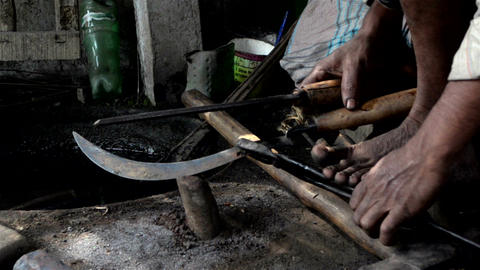 Mid close shot of filing of sickle by an Indian blacksmith Footage