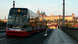 city - urban street (bridge) - Prague castle - cars and trams - people walking - Footage