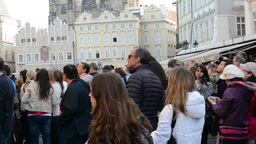 group of tourists watch the Astronomical Clock - vintage buildings - closeup Footage