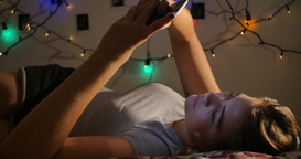 Young teenage girl relaxing on bed with social media on mobile smart phone GIF 動畫