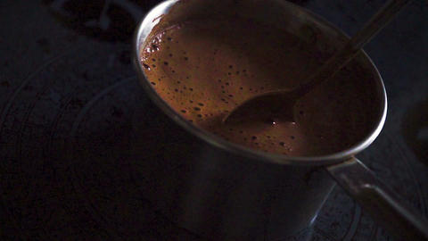 Fragrant cocoa with foam in the saucepan on the stove Archivo