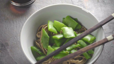 Buckwheat noodles with green beans in a ceramic bowl and sticks Footage