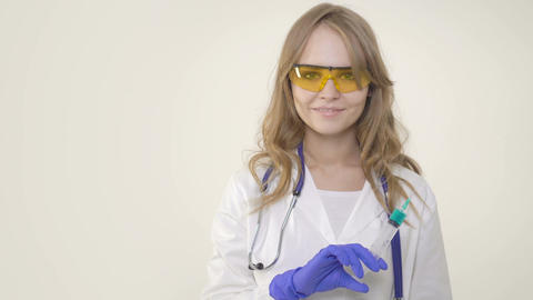 Young woman doctor smiling and holding syringe on white background Footage