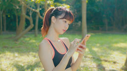 Woman use of smart cellphone in park Live影片