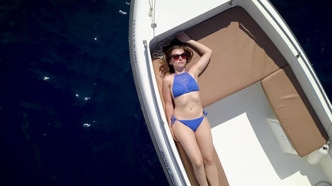 Aerial survey of a couple on a boat sunbathe together on a warm summer day Footage