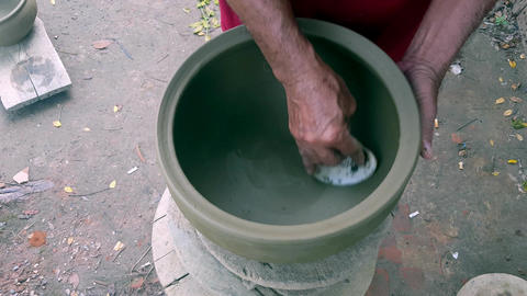 Closeup Man Hands Polish Clay Pot with Sea Mussel Shell Footage