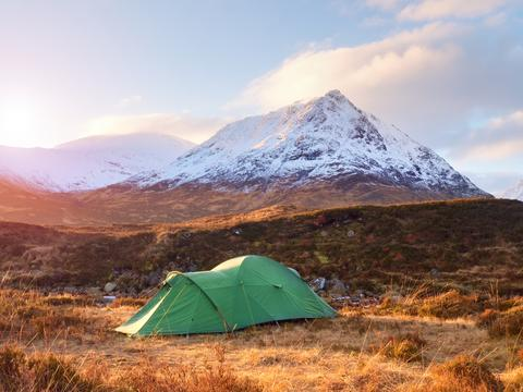Green touristic tent on meadow at river below snowy cone of mountain Stob Dearg Photo