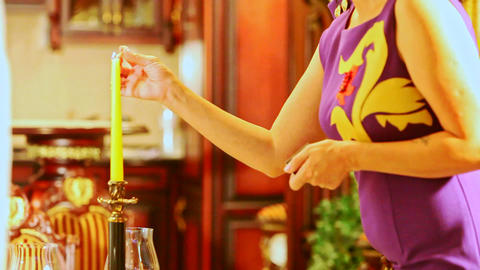 Woman Stands by Table and Strikes Match to Light Candle Footage